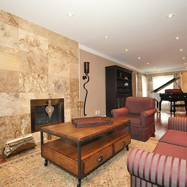 Family-Room-With-Wooden-Floors-Marble-Tiled-Fireplace-And-Wall-Mounted-Light-Fixtures